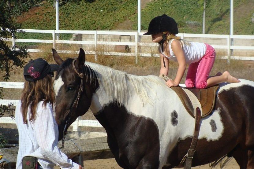 Niña aprendiendo a montar a caballo